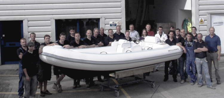 A group of people standing near by a white boat